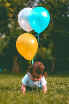 Free Baby Wearing White T-shirt Holding Three Yellow, Blue, And White Balloons On Green Grass Near Woods Royalty Free Stock Photo - 117989245