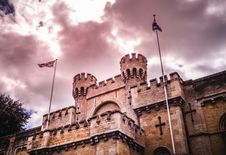 Free Castle Towers And Two Flagpoles With Flags Under Cloudy Sky Royalty Free Stock Images - 117989249