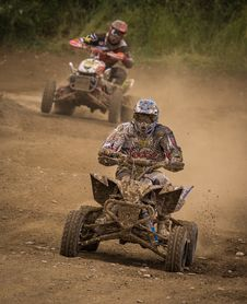 Free Man Wearing White Racing Outfit Stained With Mud Riding On Stained Mud Atv Royalty Free Stock Photography - 118221687
