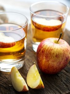 Free Sliced Apple Beside Two Apple Juice Royalty Free Stock Images - 118290559