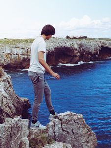 Free Man In White Shirt And Grey Pants Standing On Cliff Royalty Free Stock Images - 118290639