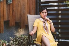Free Woman Wearing Yellow Short-sleeved Dress Sitting On Black Metal Armchair Stock Photo - 118386150