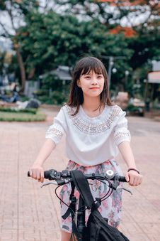 Free Woman Wearing White Blouse And Multicolored Floral Skirt Riding Bike Royalty Free Stock Photography - 118386247