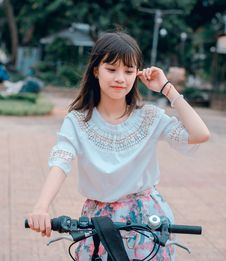 Free Woman Wearing White Blouse And Multicolored Floral Skirt Riding Bike Royalty Free Stock Image - 118386256