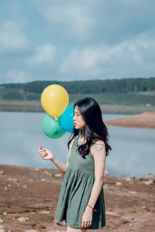 Free Woman In Green Sleeveless Dress Holding Yellow, Green, And Blue Balloons Royalty Free Stock Images - 118386289