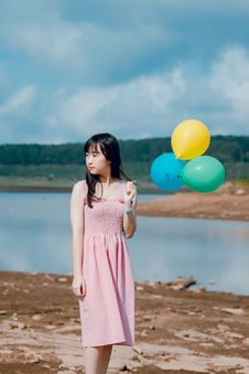 Free Woman Wearing Pink Dress Holding Three Balloons Near Body Of Water Royalty Free Stock Images - 118386299