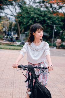 Free Woman Wearing White Blouse Riding Bicycle On Brown Concrete Tiled Area Near Trees Stock Image - 118386311
