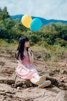 Free Woman Wearing Pink Dress Sitting On Ground Holding Two Balloons Stock Photos - 118386313