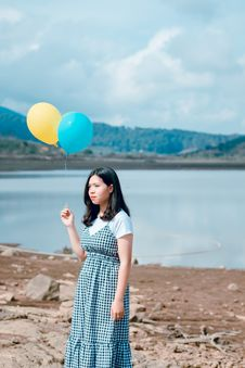 Free Woman Wearing Blue And White Plaid Dress Holding Blue And Yellow Balloons Near Calm Body Of Water At Daytime Stock Image - 118386321