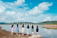 Free Six Girls Raise Their Hands In Front Of Body Of Water Stock Image - 118386331