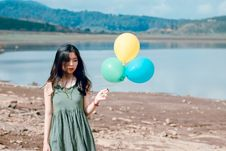 Free Woman In Green Sleeveless Dress Holding Three Balloons Royalty Free Stock Image - 118386346