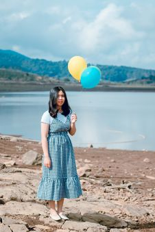 Free Woman In White And Black Dress Stands While Holding Party Balloons Stock Photo - 118386350