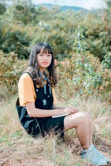 Free Girl In Black Dungaree And Orange Shirt Sitting Of Grass Field Royalty Free Stock Photos - 118386378