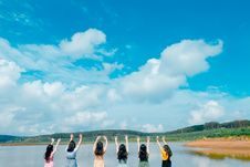 Free Group Of Women Wearing Dress Raising Up Their Hands On Air Under Cloudy Sky Stock Photos - 118386423