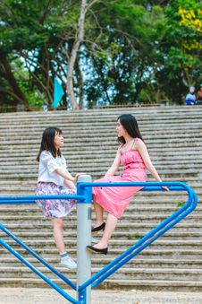 Free Two Girl Sitting On Blue Metal Rack Royalty Free Stock Images - 118464619