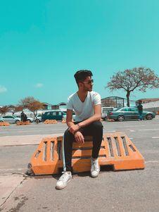Free Man In White Shirt Sitting On Orange Concrete Royalty Free Stock Image - 118464806