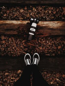 Free Person Wears Black-and-white Vans Low-top Sneakers Stands In Front Of Black Dslr Camera Stock Photo - 118464880