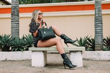 Free Woman Wearing Black And White Polka-dot Shirt With Black Short Shorts Holding Black Leather Tote Bag Sitting On White Concrete Ben Royalty Free Stock Photography - 118545987