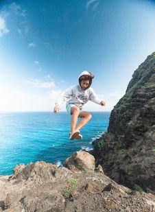 Free Man Wearing Gray Hoodie Jumping At Rock Royalty Free Stock Photography - 118598747