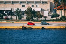Free Red And Gray Hatchbacks On Side Of Road Beside Wate R Stock Photography - 118598752
