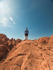 Free Man Wearing Blue Shirt And Black Shorts Standing On Top Of Brown Rock Formations Under Clear Sky Royalty Free Stock Images - 118598759