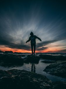 Free Person Wearing Hoodie Standing On Rock Surrounded By Body Of Water Stock Image - 118598761