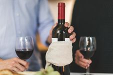 Free Man Holding White Labeled Red Wine Bottle Near Wine Glasses Stock Images - 118598974