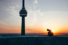 Free Silhouette Of A Man Sitting Near Black Tower Near Body Of Water During Sunset Stock Photo - 118598990