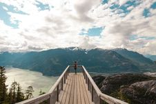 Free Person Standing With Hands On Air On Brown Wooden Dock With Overlooking View Of Lake Under White Clouds And Blue Sky Royalty Free Stock Image - 118920716