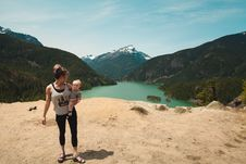 Free Woman Wearing Grey Tank Top Carrying Baby In Distant Of Lake Between Mountains Stock Image - 118920731