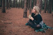 Free Woman In Black Sweater Sitting On Brown Ground While Holding Cup Stock Image - 118920781