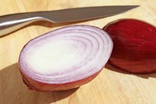 Onion On Chopping Board With Knife Stock Image