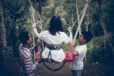 Free Two Men Assisting Woman Riding On Swing Stock Images - 119007934