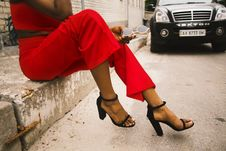 Free Woman Wearing Red Pants And Black Leather Ankle Strap Sandals Royalty Free Stock Photography - 119007967