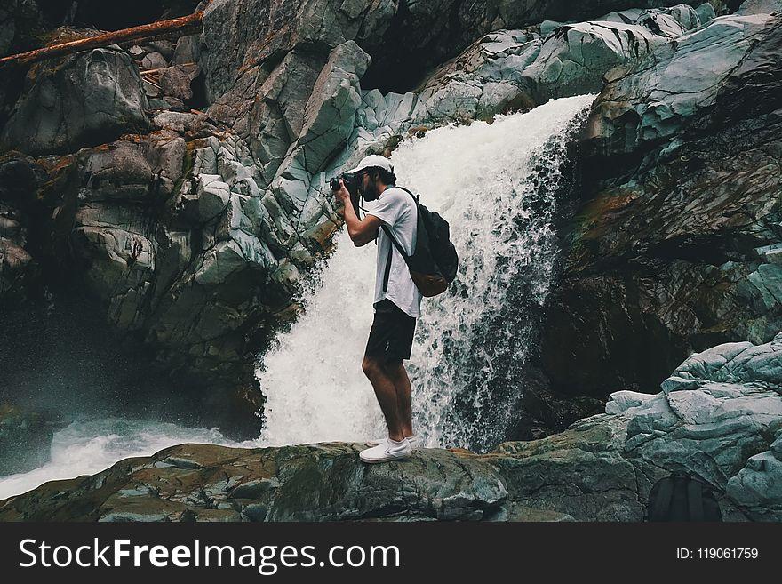 Man Wearing White T-shirt Holding Dslr Camera Near Waterfall