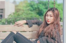 Free Woman In Black Button-up Long-sleeved Shirt Sitting On Brown Swing Bench Stock Images - 119196844