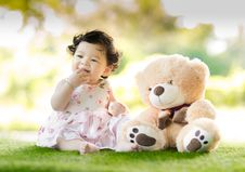 Free Baby Sitting On Green Grass Beside Bear Plush Toy At Daytime Stock Photos - 119308713