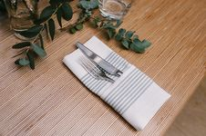Free Silver Fork And Knife Inside Gray And White Table Napkin On Table Royalty Free Stock Image - 119308716