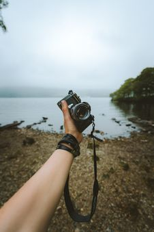 Free Person Holding Black Camera Front Body Of Water Royalty Free Stock Photo - 119467405