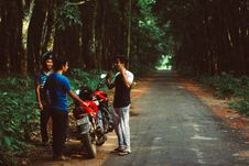 Free Three Men Standing Beside Red Motorcycle Surrounded With Green Trees Royalty Free Stock Photography - 119467637