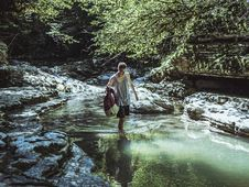 Free Man Walking On River In Between Stone And Tree Royalty Free Stock Photos - 119467738
