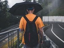 Free Man Wearing Orange Shirt Holding Black Umbrella Stock Photography - 119467762
