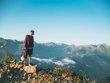 Free Man In Red Sweatshirt And Black Shorts Standing On Large Brown Rock On Top Of A Mountain Royalty Free Stock Photo - 119554135