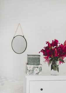 Free Red Flower Centerpiece On White Wooden Drawer Dresser Royalty Free Stock Photos - 119554258