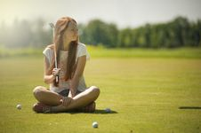 Free Woman In White Scoop-neck Shirt And Blue Shorts Holding A Golf Club Sitting On Golf Field Stock Images - 119554264