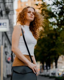 Free Woman In White Turtleneck Sleeveless Top And Brown Bottoms Holding Black Leather Crossbody Bag Outfit Stock Images - 119554304