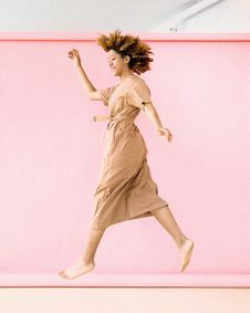 Free Woman Wearing Brown Dress Jump Near Pink Wall Royalty Free Stock Images - 119554329