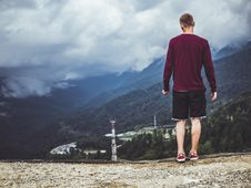 Free Man Wearing Maroon Sweater And Black Shorts Standing In Front Of Mountain Stock Photo - 119611230