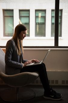 Free Woman Sits And Use Laptop Computer Near Window Royalty Free Stock Photo - 119611485