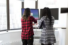Free Two Women Standing In Front Of Television Stock Image - 119666391
